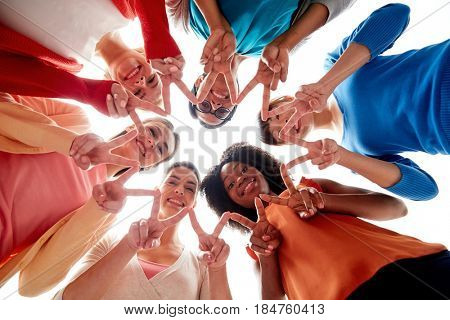 diversity, race, ethnicity and people concept - international group of happy smiling different women lying on floor in circle and showing peace hand sign
