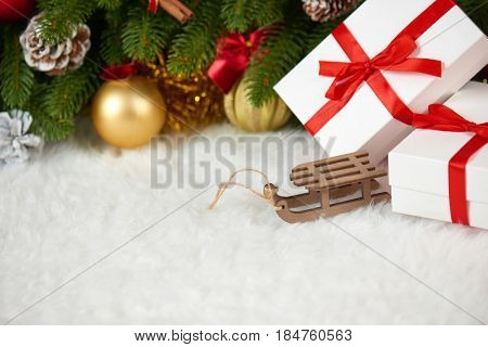 christmas decoration on fir tree branch closeup, wooden sledge toy, gifts, xmas ball, cone and other object on white blank space fur, holiday concept, place for text