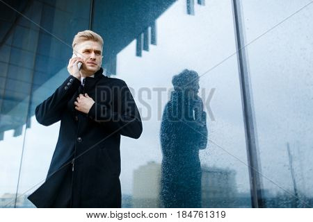 Low angle view of serious white collar worker looking away while discussing joint project with colleague on smartphone and standing at modern glass office building, portrait shot