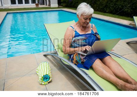 Senior woman using laptop on lounge chair at poolside