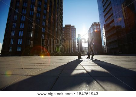 Low angle view of two unrecognizable businessmen shaking hands firmly while standing outdoors, last beams of setting sun illuminating them, lens flare