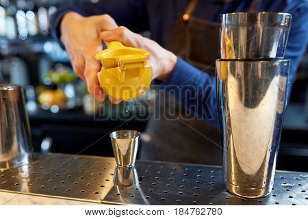 alcohol drinks, people and luxury concept - bartender with shaker and citrus squeezer squeezing juice into jigger and preparing cocktail at bar