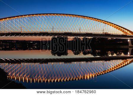 Troja Bridge in Prague over the Vltava River. Beautiful view at dusk, mirroring lines of construction in the river. Early on the Vltava river. Trojsky most . Czech Republic