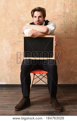 business and education marketing concept tired man in suit with blackboard on chair on beige background crisis and bankruptcy unemployment overtime