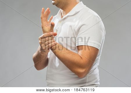 people, healthcare and problem concept - close up of man suffering from pain in hand over gray background
