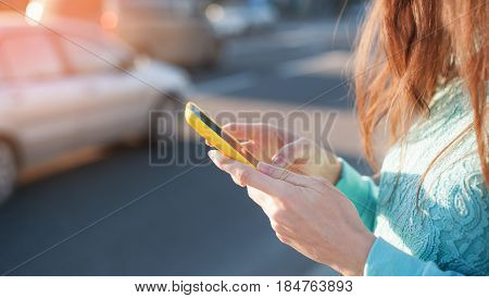young woman with a smartphone rewrites on her way to work