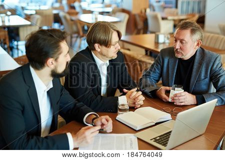 Three confident business partners in formalwear discussing new contract terms before signing it while sitting in spacious restaurant, waist-up portrait