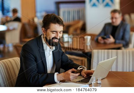 Waist-up portrait of smiling middle-aged businessman texting with his friend on modern smartphone while sitting in cafe and working on laptop