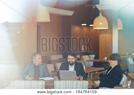Productive project discussion with colleagues: three bearded businessmen in formalwear gathered together in cozy cafe and brainstorming, view through panoramic window