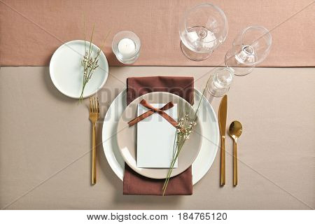 Beautiful table setting with golden flatware