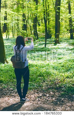 Young woman take a photo with smart phone on a pathway in the forest. Beautiful woman with bag. Nature. Deciduous trees. Spring time. Pleasure weather and sun light