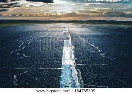 Long Airport runway with marking at twilling time.