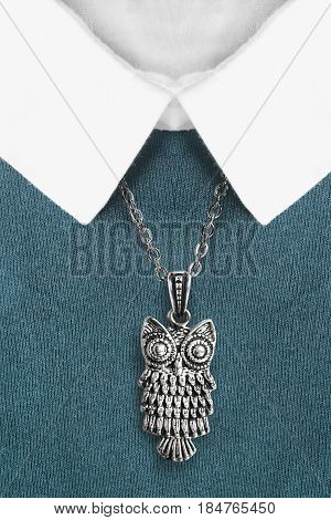 Silver owl pendant over blue pullover with white collar closeup
