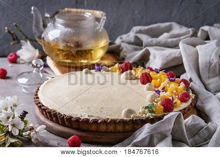 Homemade chocolate tart decorated by mango, raspberries, mint, puffed rice and edible flowers served with glass teapot and textile linen over gray texture table. Rustic style. Comfort food concept.