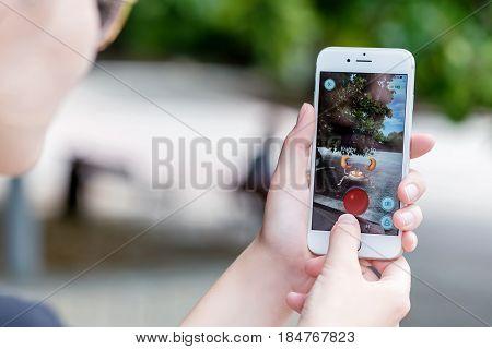 Varna Bulgaria - Jul 20 2016: A woman battles Krabby pokemon while playing the Nintendo augmented reality mobile game Pokemon Go on an Apple iPhone 6S.