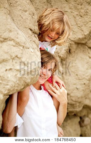 blond girl with mother- gil sitting on mothers shoulders