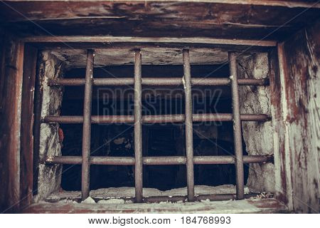 Lattice on the window, in the wall of the old prison. Russia, Magadan