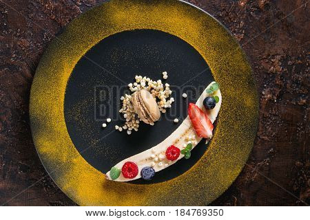 Food plating dessert organic banana with fresh berries, mint, puffed rice and macaroon biscuit served with turmeric powder on black plate over brown texture background. Flat lay, space