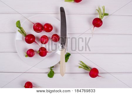 Spring fresh radishes on white plate with knife ready for salad. Radishes background