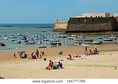 CADIZ, SPAIN - SEPTEMBER 8, 2008 - Tourists relaxing on La Caleta beach with the harbour and Castle to the rear Cadiz Cadiz Province Andalusia Spain Western Europe, September 8, 2008.