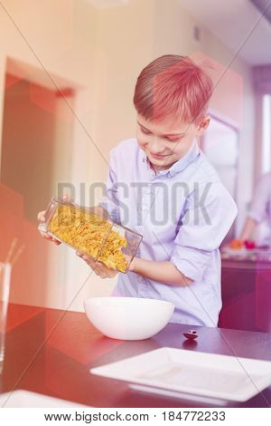 Smiling boy pouring corn flakes in bowl at home