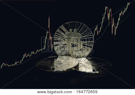 Three Shiny Bitcoin Coins On Black Background With Trading Chart