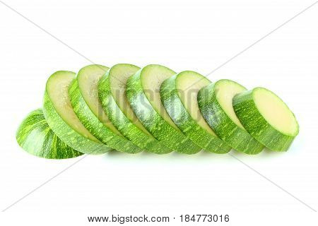 Green zucchini sliced in round slices isolated on white background.