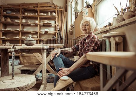 Happy Senior Woman Sitting On Bench Near Window At Workshop