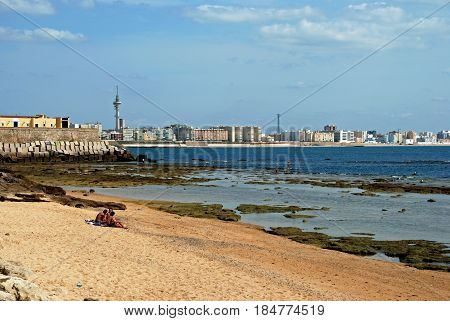 CADIZ, SPAIN - SEPTEMBER 8, 2008 - Tourists relaxing on La Caleta beach with views across the bay to the Southern side of the city Cadiz Cadiz Province Andalusia Spain Western Europe, September 8, 2008.