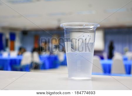 cold water in glass-plastic in seminar conference room background. select focus with shallow depth of field