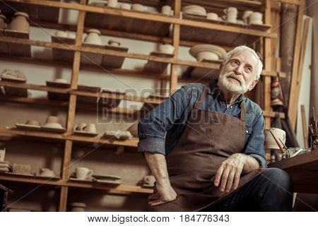 Senior Potter In Apron Sitting At Table And Daydreaming At Manufacturing