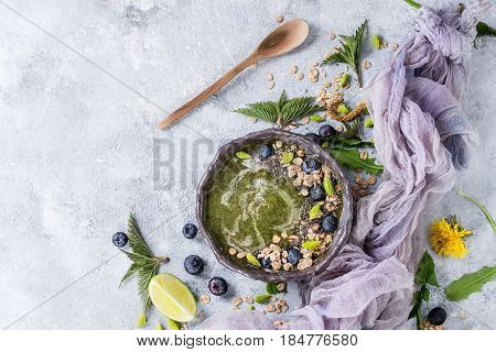Spring green nettle and dandelion smoothie bowl served with lime, yellow flowers, young leaves, oat flakes, chia seeds, blueberries, gauze and spoon over gray blue texture background. Top view, space