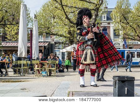 AMSTERDAM , NETHERLANDS - APRIL 31, 2017 : Scottish bagpiper tuning his instrument in the streets of Amsterdam wearing his Royal Stuart tartan kilt and plaid