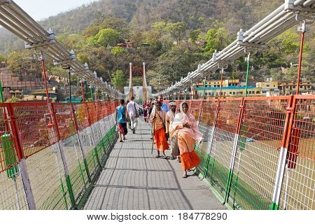 INDIA, LAXMAN JHULA - APRIL 8, 2017: People walking on the suspension bridge in Laxman Jhula on the 8th of april 2017