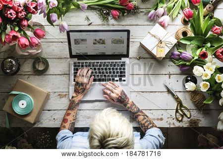 Woman Using Laptop Searching on Internet to Shop Flowers Plants Online