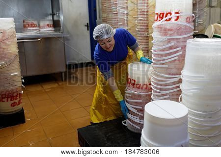 ST. PETERSBURG, RUSSIA - FEBRUARY 28, 2017: Female worker taking a stack of empty containers for pickles. The Factory of Homemade Pickles participates in the regional quality certification program