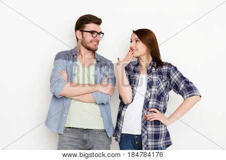 Happy couple. Playful woman flirting with boyfriend, studio shot, white isolated background