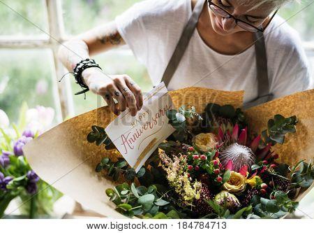 Florist Making Fresh Flowers Bouquet Arrangement with Happy Anniversary Card