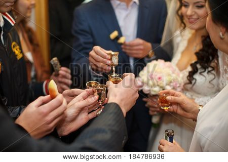 A closeup of guests' hands while they clang glasses with newlyweds