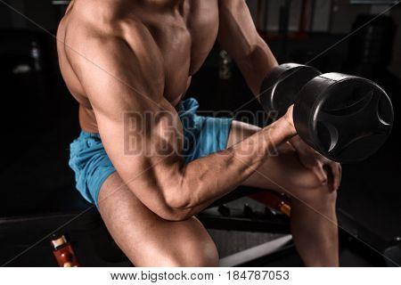 Very power athletic guy bodybuilder execute exercise with dumbbells at dark gym. Muscular man. Part of the body