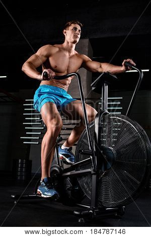 Portrait of a physically fit man in modern fitness center. Muscular man on a bicycle in the gym