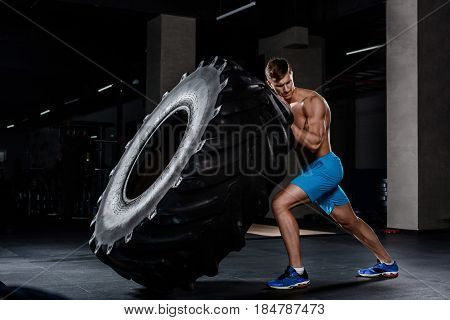 Crossfit training - man flipping tire in gym. A muscular man pushes a big tire