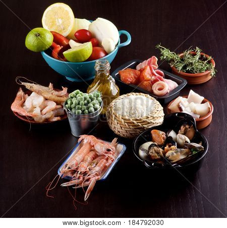 Raw Ingredients of Spanish Traditional Paella with Various Seafood Mussels Vegetables Rice Green Pea and Olive Oil closeup on Dark Wooden background