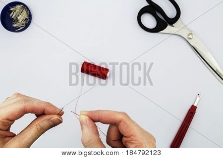 Female threading a sewing needle with red cotton