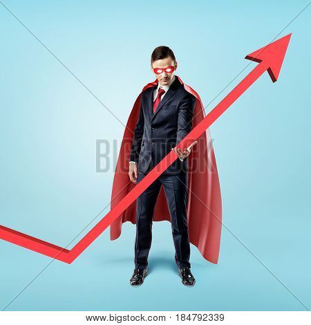 A businessman in a red flowing cape trying to keep the upward looking red arrow with his hand. Investment and money. Stock index. Growing market.