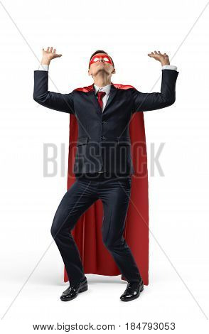 A businessman in superhero costume over his suit trying to hold a heavy invisible heavy object from above. Business trials. Choosing the workload. Unexpected problems.