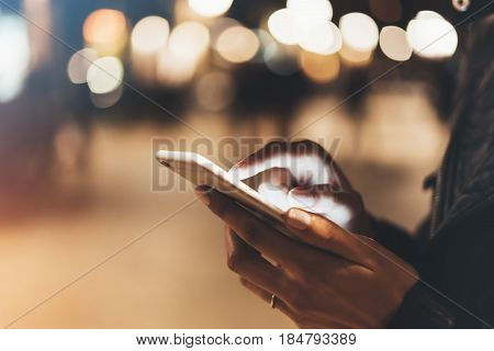 Girl pointing finger on screen smart phone on background illumination color light in night atmospheric city hipster using in female hands and text mobile phone mock up glitter street content lifestyle