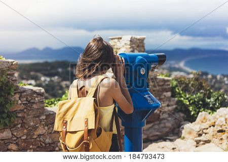 Hipster tourist look observant binoculars telescope on panoramic view lifestyle concept trip traveler with backpack on background mountain and blue sea landscape horizon young girl hiker pointing hands