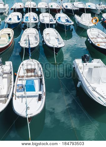 Some boat bright colors on background blue water lake of pier fishing and boating on summer landscape holiday travel and sun tourism coast peaceful ship on backdrop old house and ocean