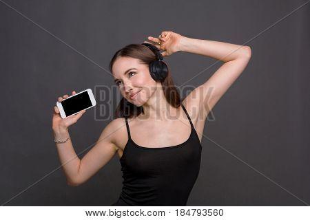 Favorite playlist. Woman enjoying music from mobile in earphones dancing on gray studio background